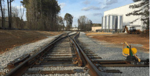 closeup of new rail and track switch with silos and large building in background