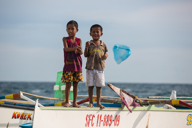 San Agustin community children find joy in playing with a plastic bag by sea on a fishing boat. Photo taken by EXPOSURE PH.