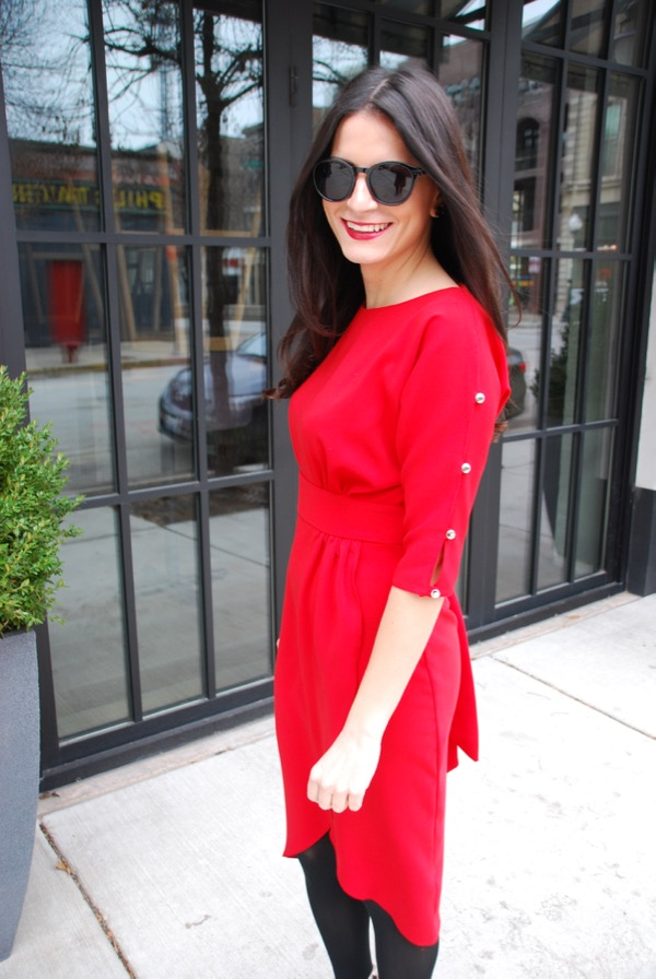 smiling in a red wrap dress with shoulder details