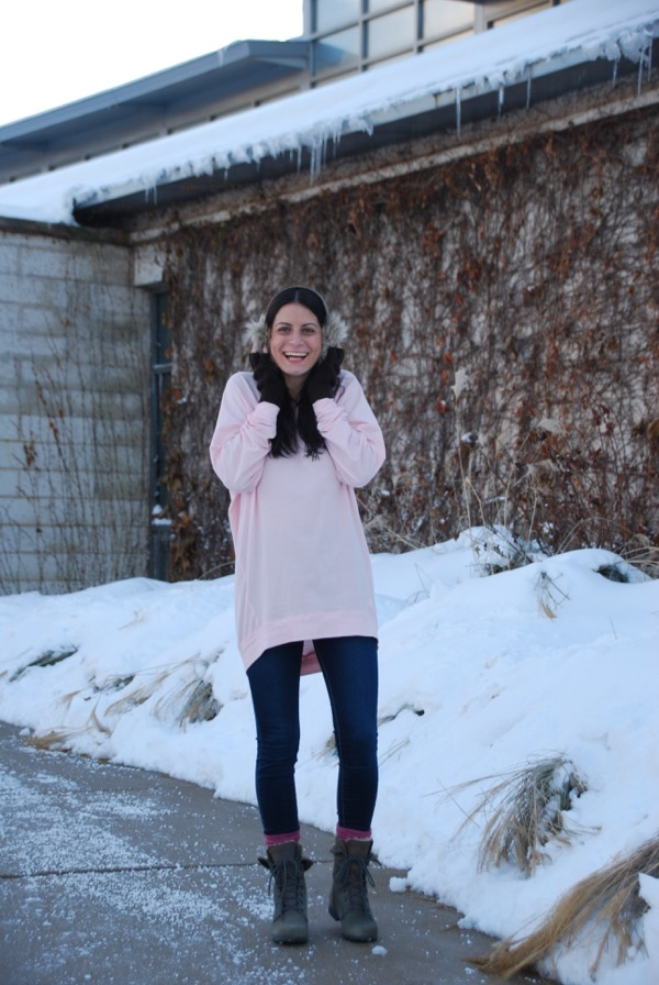 smiling in a cozy slouchy tunic and earmuffs