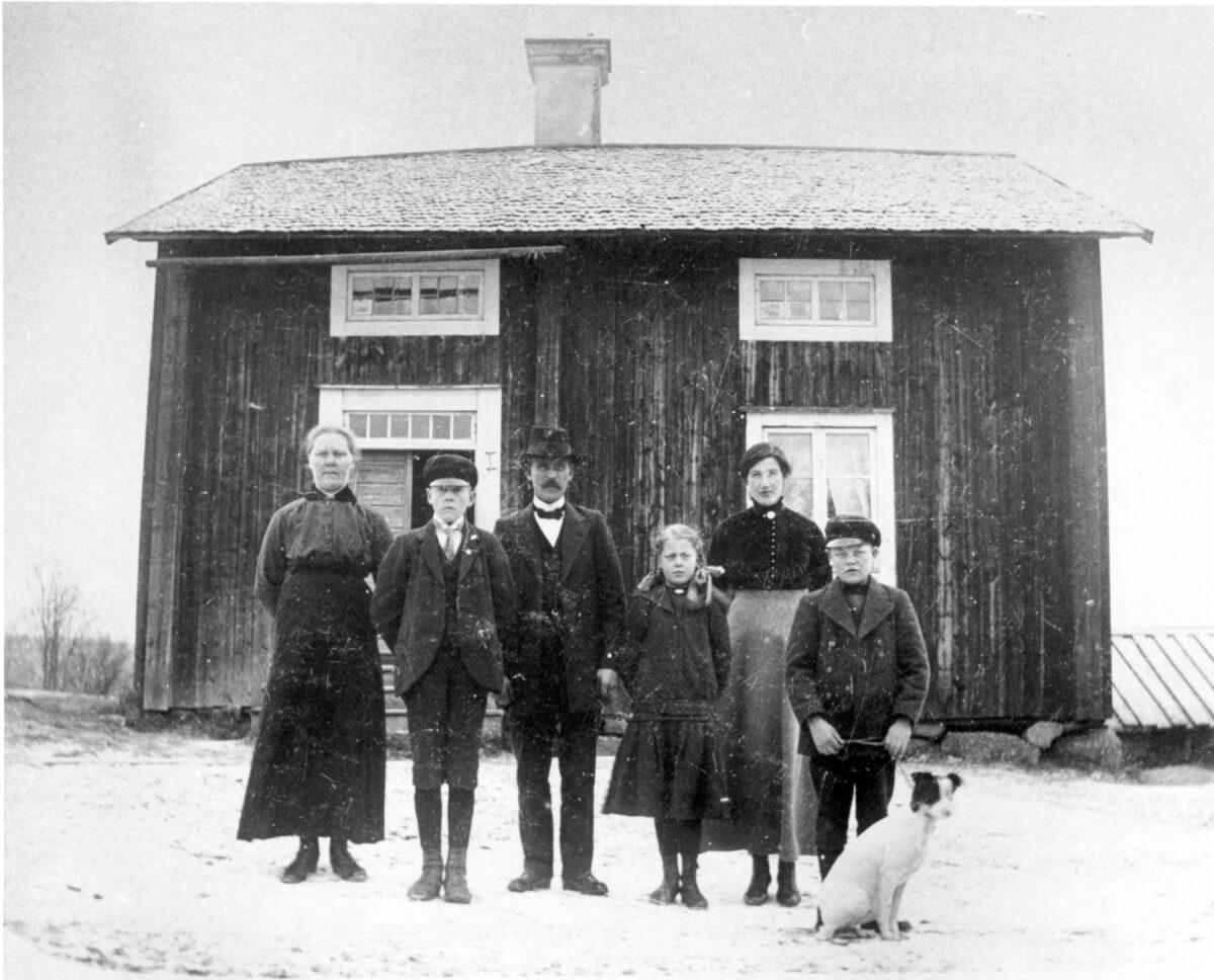 En familjebild tagen framför ett hus.