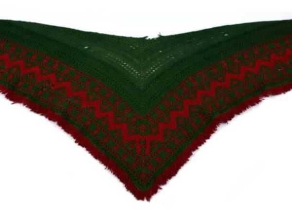 Hjärtvärmare av grönt garn med röda detaljer.