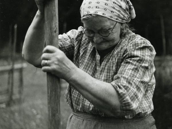 En gammal kvinna håller upp en kraftig trästång med bägge händerna. Hon har runda glasögon, ett huckle över håret, smårutigt förkläde. Man ser att hon håller stången i ett fast grepp med sina starka händer. Bilden är tagen på landet, man ser en mörk skog i bakgrunden.
