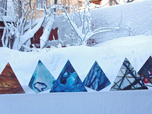 Trekantiga, mönstrade urnor i olika färger mot ett snöigt landskap.