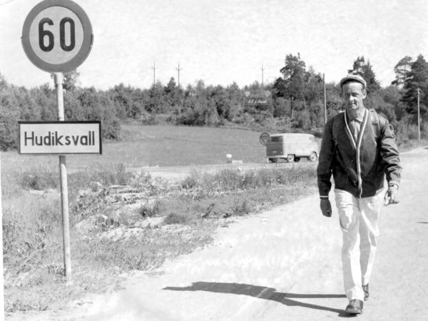 """En man går längs en väg och till vänster om honom står """"Hudiksvall"""" på en skylt."""