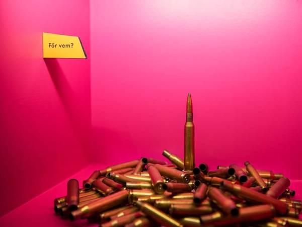 """En hög med ammunition bredvid en skylt där det står """"För vem?"""""""