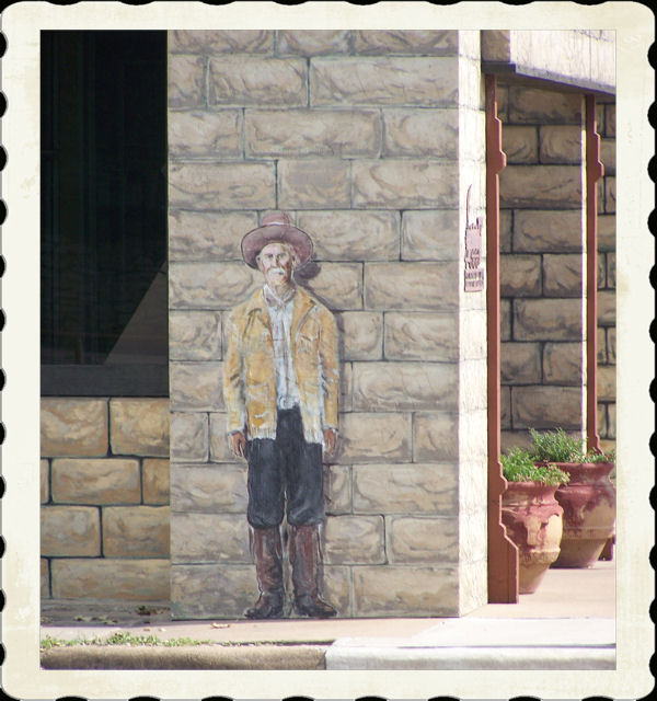 Life size cutout of Brushy Bill attached to the bank building in Hico accross the street from the Billy the Kid statue.