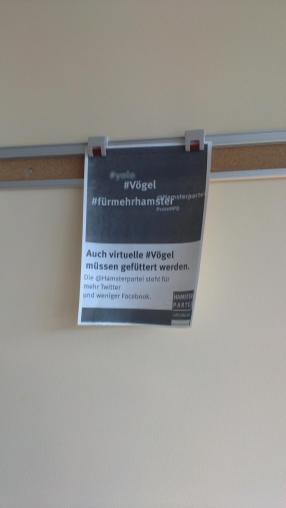 An Wandklemmen befestigt hängt stolz das Twitterplakat der Hamsterpartei an einer Wand.
