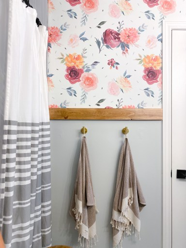 watercolor floral peel and stick wallpaper in a bathroom with hold towel hooks