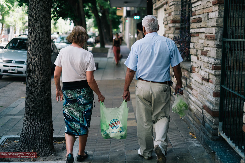 2 old people carrying a bag