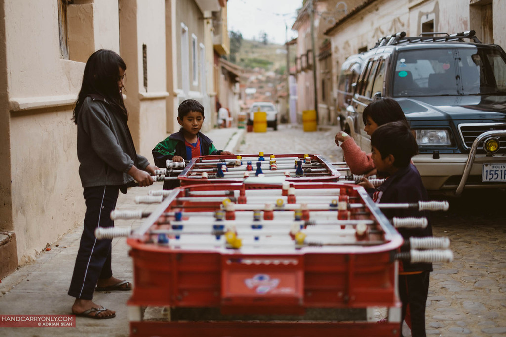 kids playing table football, tarabuco, bolivia
