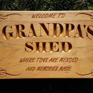 Wooden sign engraved Welcome to Grandpa's Shed where toys are mended and memories made