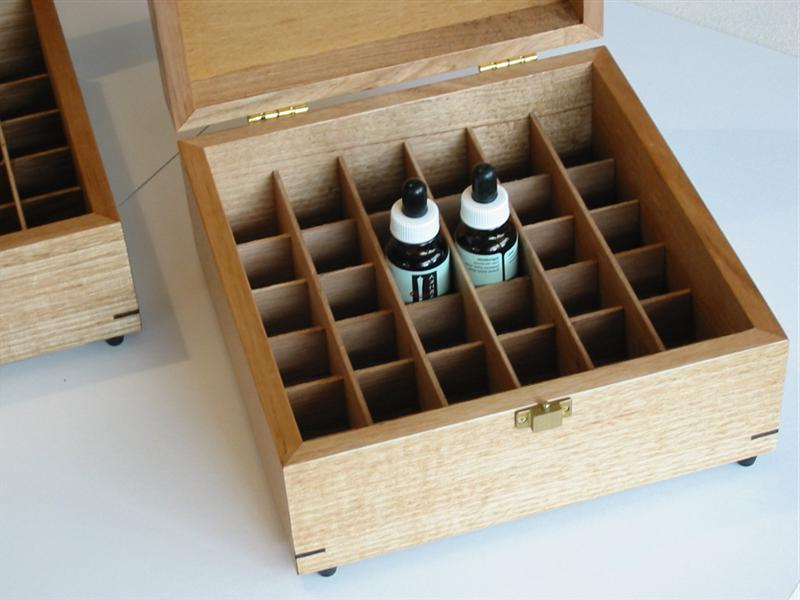 Close up photo of a wooden box with dividers for storing oils bottles
