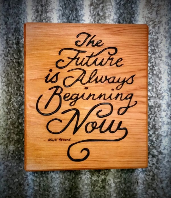 Front view of engraved wood quote magnet reads the future is always beginning now by mark strand