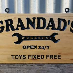 Pine sign with carved black engraved lettering and black screw eyes for easy hanging. Reads 'Granddad's workshop open 24/7 toys fixed free'