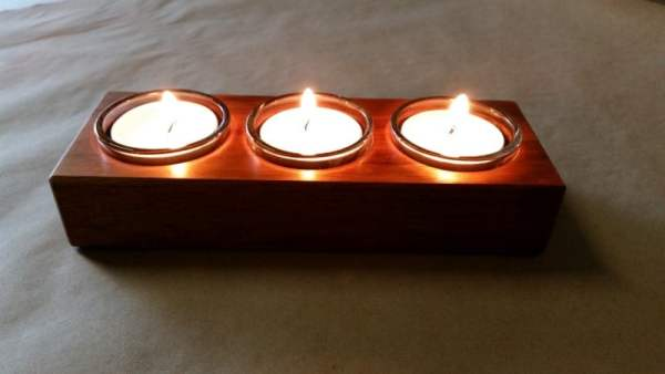 closeup of tealight candle holders in use showing the reflections of lit flame off the timber surface