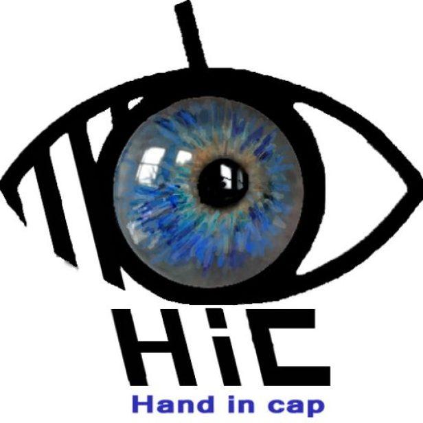 """Logo de mon blog """"Hand in Cap"""". Il s'agit de mon oeil, bleu, en gros plan, dans lequel on voit le reflet d'une fenêtre et qui est inséré dans le pictogramme noir symbolisant le handicap visuel. En dessous est écrit """"Hand in Cap"""", expression d'origine anglaise qui signifie """" la main dans le chapeau"""" et qui est l'étymologie du mot Handicap."""