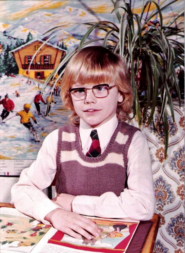 photo d'école traditionnelle Thierry VAN DEN BIL à 7 ou 8 ans.  Il est blond, souriant, porte une cravate et  est assis à une table les bras croisés au-dessus d'un album jeunesse. Il a un strabisme à l'oeil gauche.