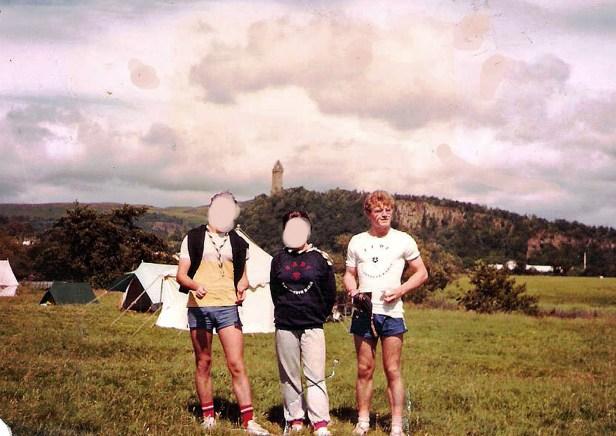 photo de Thierry VAN DEN BIL lors du Camp Eclaireurs de France 1985, à Stirling, Ecosse (année de sa totémisation, Kinkajou) Il pose avec 2 amis éclaireurs dont les visages sont floutés. Au loin, le Monument William Wallace, sur la colline d'Abbey Craig