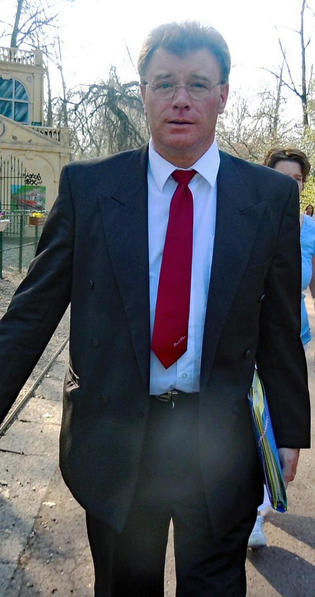 Photo en couleur de thierry van den bil portant un costume noir et une cravate rouge sur chemise blanche. Il marche dans un parc, le jardin Vauban à Lille