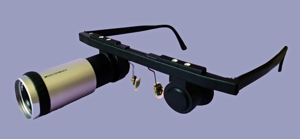 Photo qui présente une monture de lunettes sur laquelle est fixée, à l'oeil droit, une loupe télescopique. A l'oeil gauche est fixé un cache-oeil en caoutchouc ayant la forme d'une ventouse. L'ensemble est noir, à l'exception de la loupe qui est essentiellement gris aluminium. Les ponts - qui posent les lunettes sur le nez - sont en plastique souple transparent. Le fond de la photo est mauve clair.