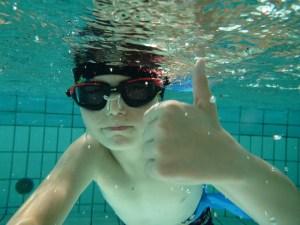 """Un jeune nageur sous l'eau faisant le signe """"tout va bien"""""""