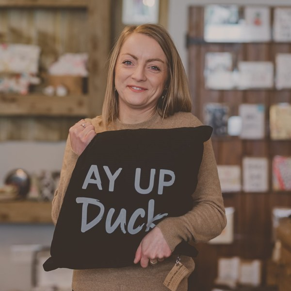 Laura Cooper Owner of Handmade Design holding an Ay Up Duck Cushion she designed