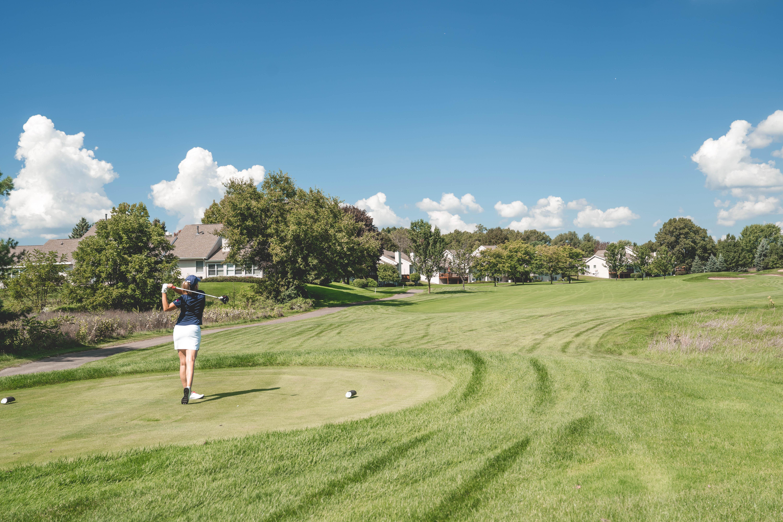 Golf woman teeing off