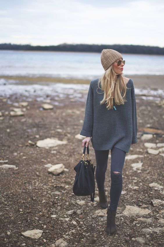 fall capsule wardrobe ideas - woman wearing a grey oversized sweater walking on the beach