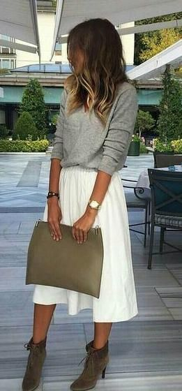 woman wearing a grey sweater with a white skirt and ankle boots