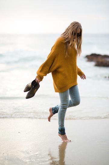 Girl wearing a mustard colour oversized knitted sweater at the beach