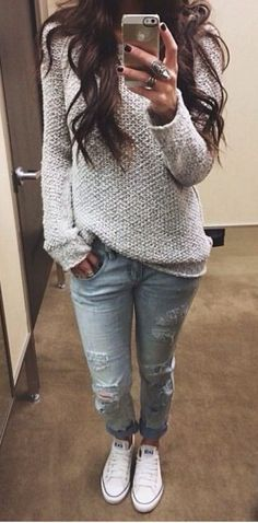woman wearing a white oversized sweater and distressed jeans