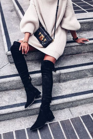 woman wearing knee high black suede boots and an oversized sweater