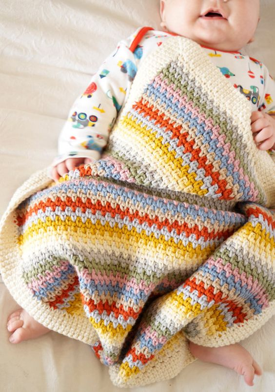 baby wrapped in a colourful crochet blanket