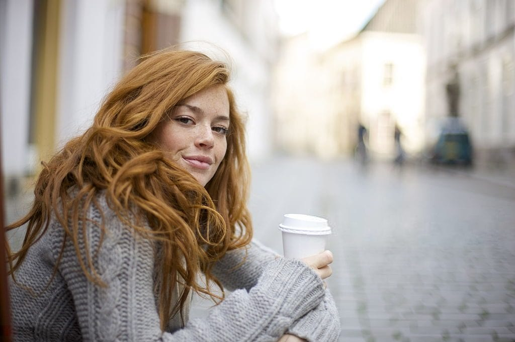 Girl with red hair wearing a grey cable knit sweater