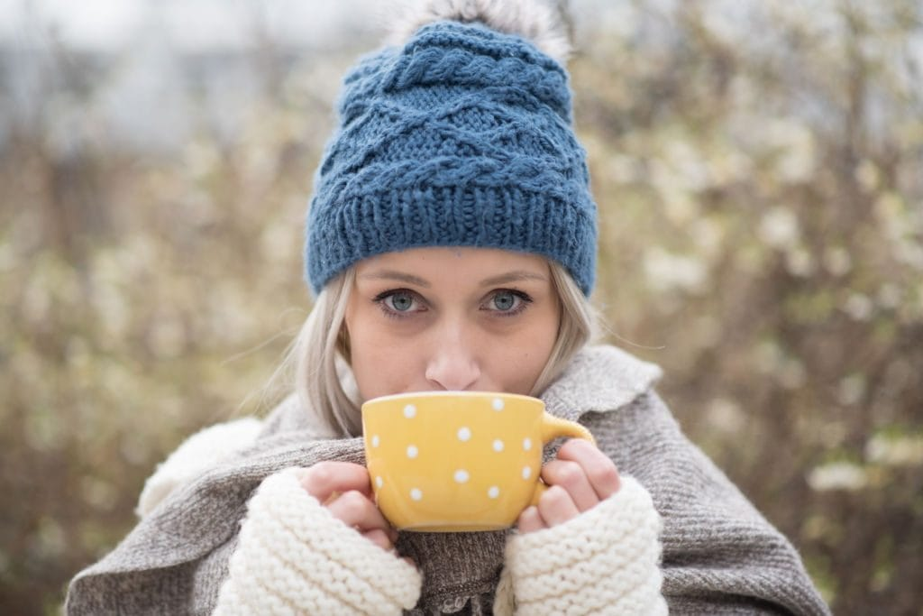 holiday favourites including a knitted hat, knitted arm warmers and a hot cup of coffee