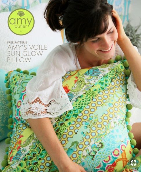 woman holding a brightly colored printed pillow