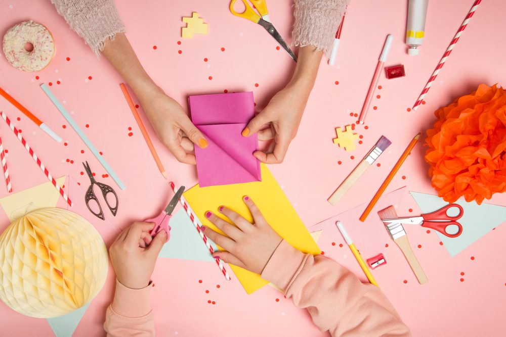crafting with paper on a pink surface