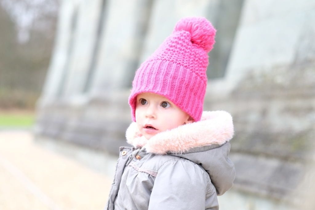 little girl wearing a pink knitted hat
