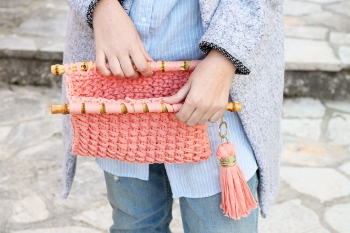 Woman opening a knitted clutch bag with bamboo handles