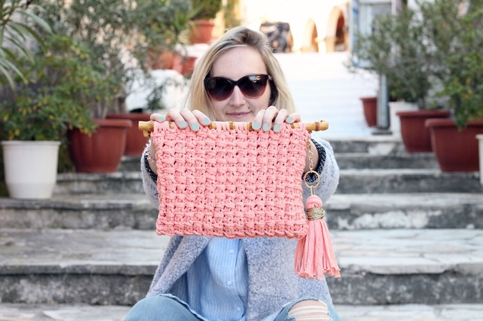 Woman holding a clutch bag knit with the bamboo stitch