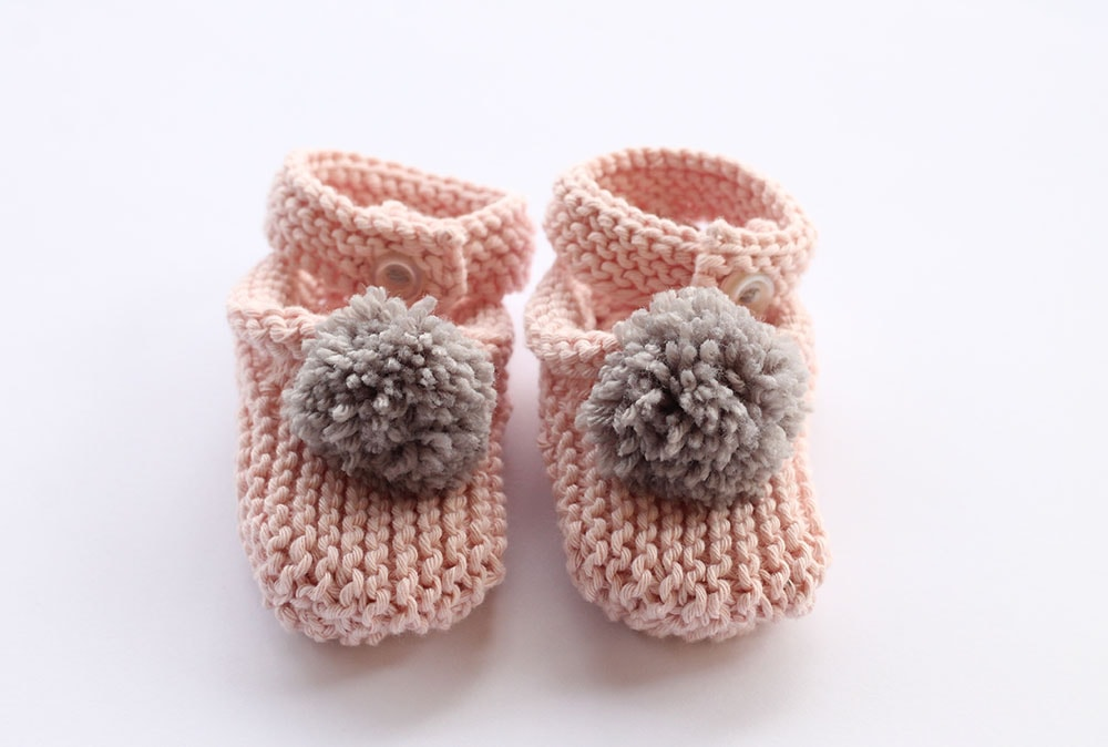 Baby slippers with pom pattern