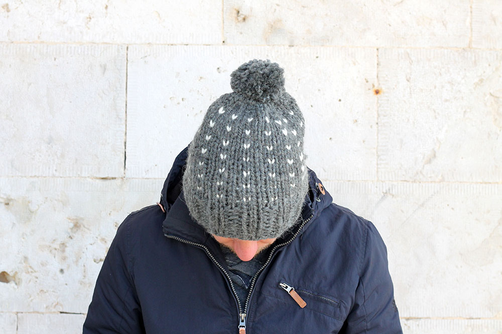 Man with his head down wearing a grey knit hat