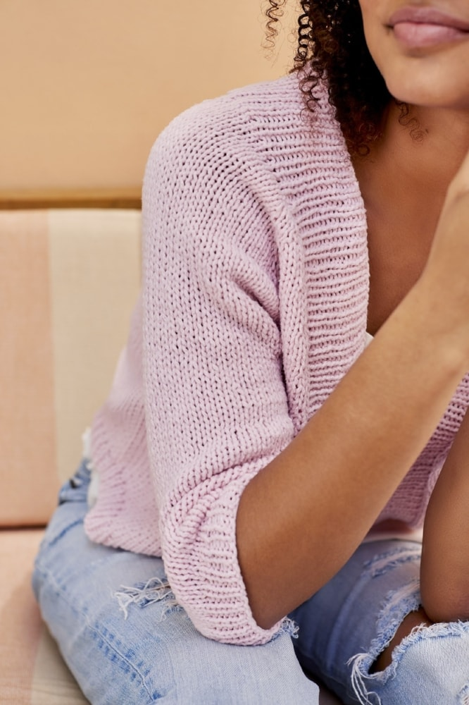 woman wearing a pink knitted cardigan