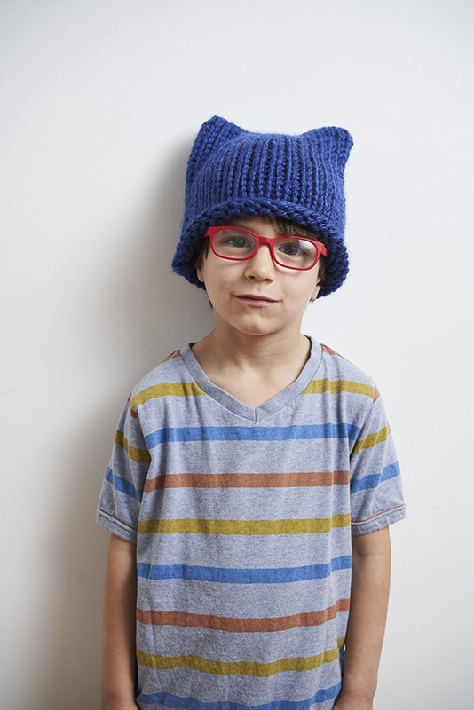 child wearing a blue knit cat hat