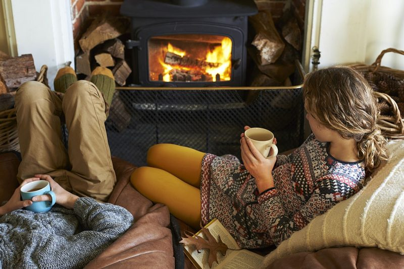 fall home decor ideas people relaxing with coffee next to a fall fireplace