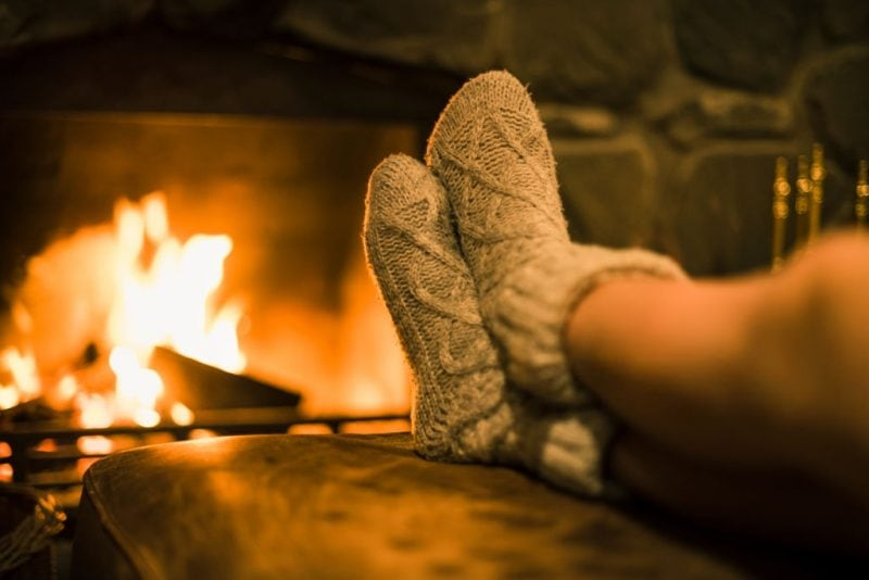 fall home decor ideas cosy knitted socks beside an open fire