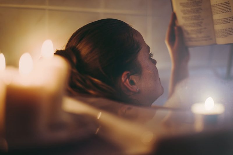 woman reading in the bathtub with candles