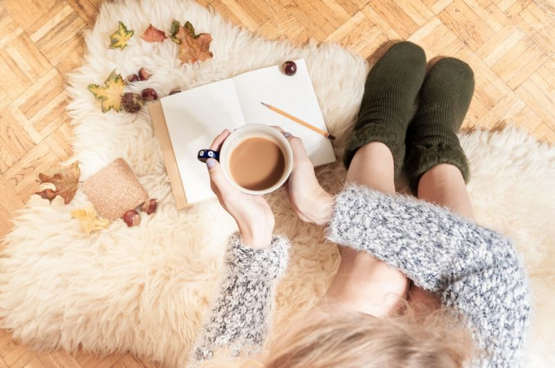 fall home decor ideas a woman reading on a faux fur rug with tea