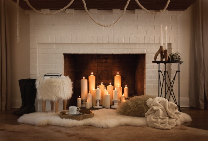 holiday fireplace with candles and fur rugs
